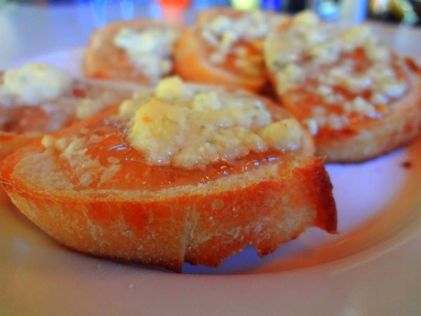 Toasted crostini with mayhaw jelly and gorgonzola cheese